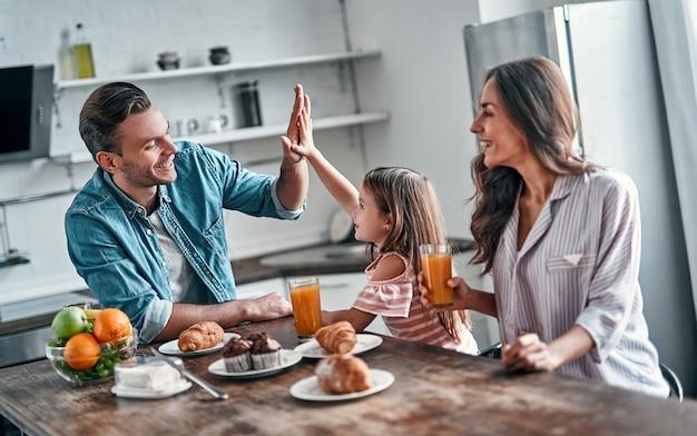 Dando high five para o papai enquanto comia na cozinha. família feliz está gostando de passar algum tempo juntos em pé na cozinha moderna leve.