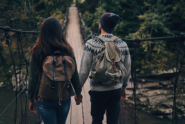 Dando o próximo passo. vista traseira de um jovem casal pisando na ponte suspensa durante uma caminhada na floresta