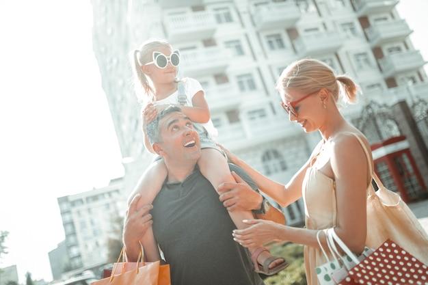 Dando suporte. homem alegre, segurando a filha nos ombros, caminhando com ela e sua esposa num dia de verão.