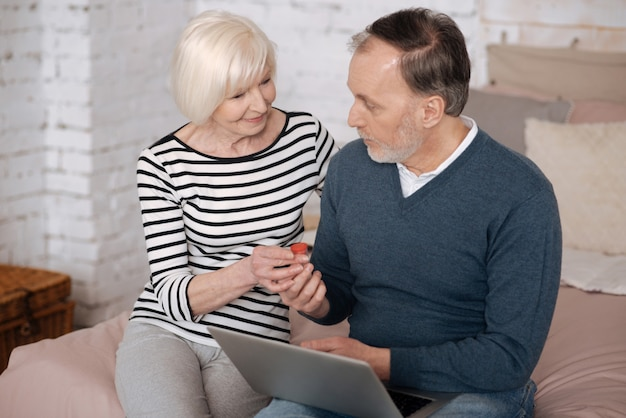 Dando suporte. senhora sênior dando um remédio para o marido usando o laptop enquanto está sentado na cama.
