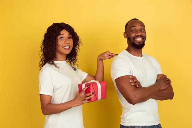 Dando surpresa. celebração do dia dos namorados, feliz casal afro-americano isolado no fundo amarelo do estúdio. conceito de emoções humanas, expressão facial, amor, relações, férias românticas. Foto gratuita