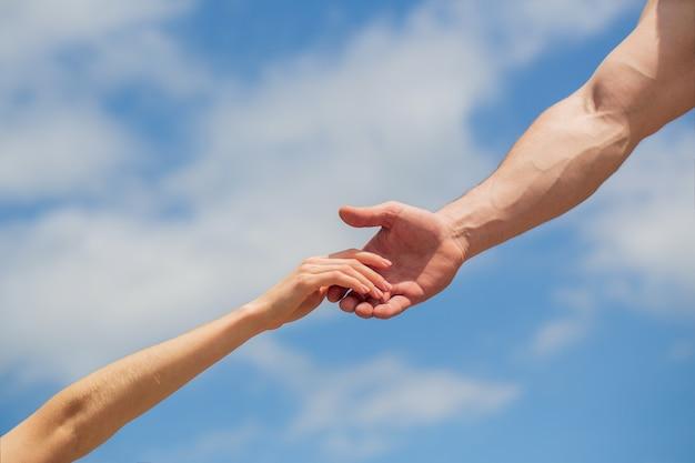 Dando uma mão amiga. mãos de homem e mulher no fundo do céu azul.
