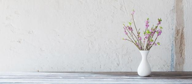 Daphne flores em um vaso na mesa de madeira velha na parede branca