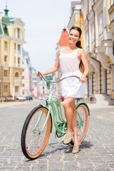 Dar um passeio. comprimento total de uma jovem atraente e sorridente em pé perto de sua bicicleta na rua