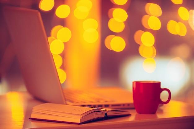 Dar um tempo! imagem de close-up do local de trabalho com laptop, xícara de café e luzes de natal ao fundo