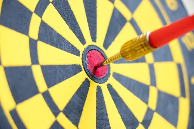 Dardo de seta vermelha atingiu no centro do fundo de alvo de cor preta e amarela