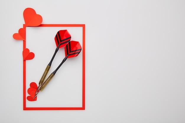Dardos vermelhos de dia dos namorados e coração de papel