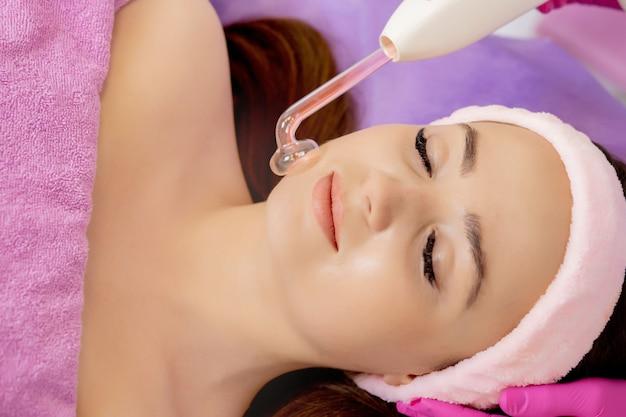 Darsonvalização da face ou rejuvenescimento da face com auxílio da eletroterapia. foto de darsonval para o rosto. terapia atual. a paciente está na esteticista.
