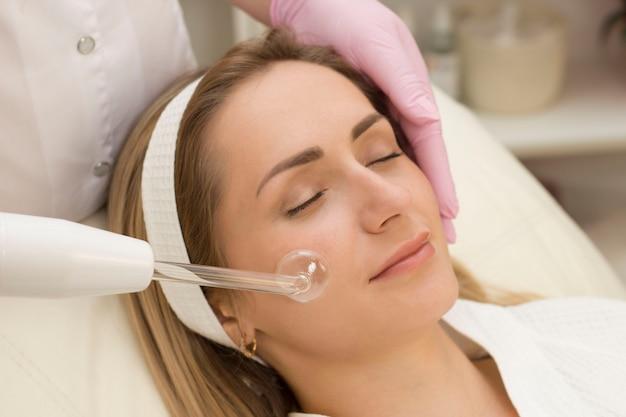 Darsonvalização da face ou rejuvenescimento da face com auxílio da eletroterapia.