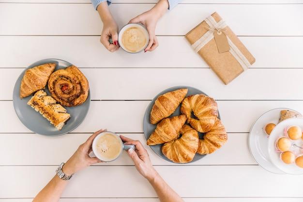 Das mãos acima da colheita durante o café da manhã