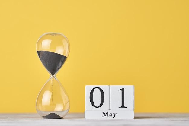 Data 1 de maio e ampulheta em um fundo amarelo