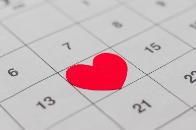 Data de 14 de fevereiro no calendário, coração vermelho do dia dos namorados cercado.