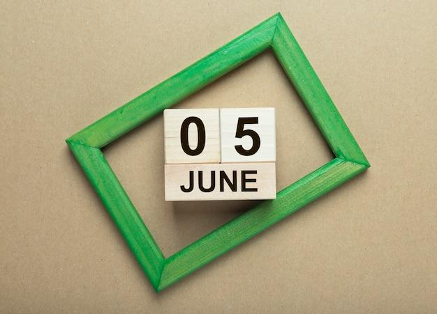 Data de 5 de junho no calendário de madeira no fundo do ofício.