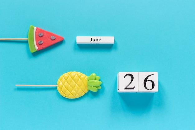 Data de calendário 26 de junho e frutas de verão abacaxi de doces, pirulitos de melancia