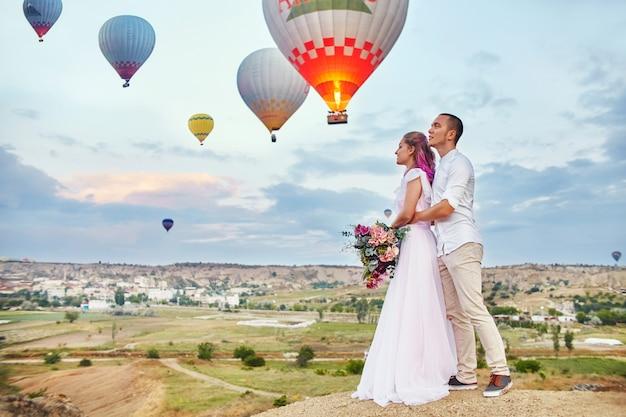 Data de um casal apaixonado ao pôr do sol contra de balões na capadócia