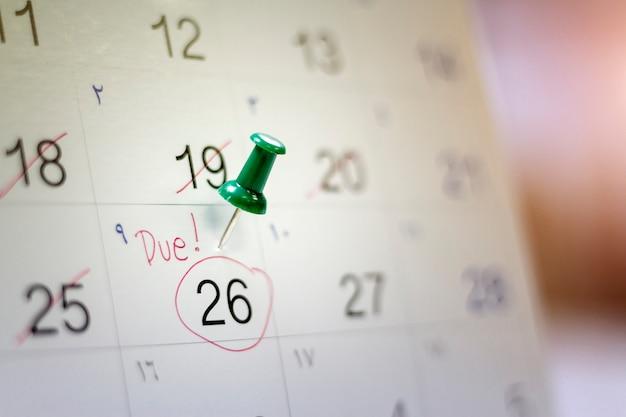 Data de vencimento do pagamento escrita em um calendário com um alfinete verde para lembrá-lo e compromisso importante