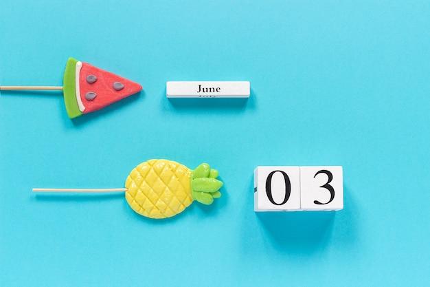 Data do calendário 03 de junho e frutas de verão abacaxi doce, pirulitos de melancia.