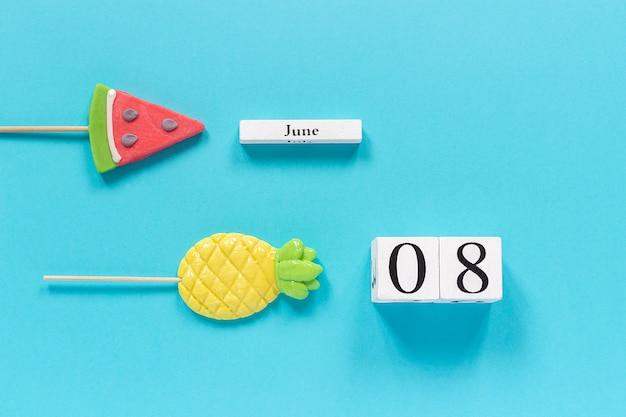 Data do calendário 08 de junho e frutas de verão abacaxi doce, pirulitos de melancia.