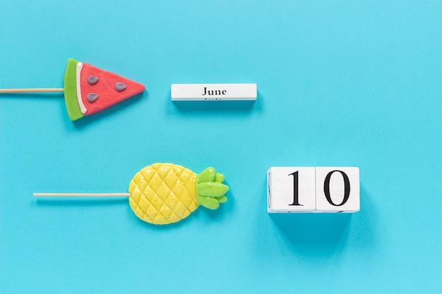Data do calendário 10 de junho e frutas de verão abacaxi doce, pirulitos de melancia.