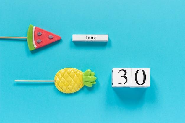 Data do calendário 30 de junho e frutas de verão abacaxi doce, pirulitos de melancia.