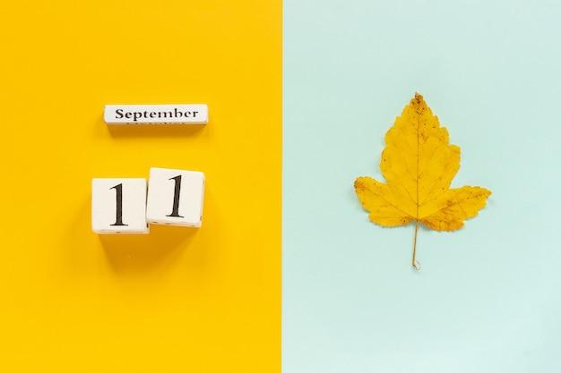 Data do calendário e folha de outono amarela