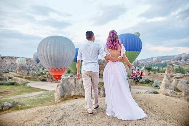 Data do casal apaixonado ao pôr do sol contra balões