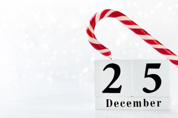 Data do dia de natal no calendário. calendário de madeira show de 25 de dezembro com pirulito vermelho e branco