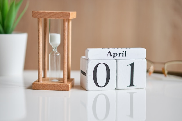 Data em cubos de madeira brancos - primeiro de 1º de abril em uma mesa branca.