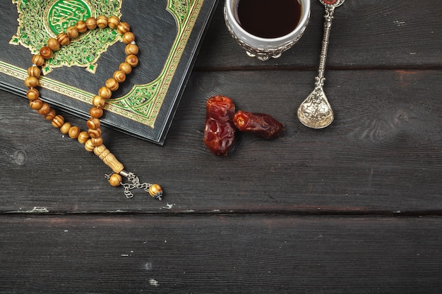 Data frutas, alcorão e rosário de madeira sobre o ramadã muçulmano de madeira, mensagem abençoada sexta-feira e três meses