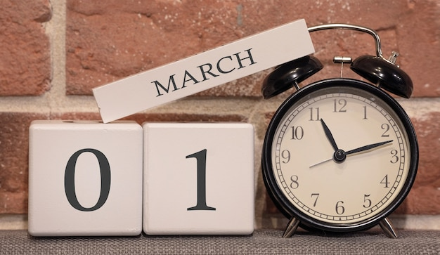 Data importante, 1º de março, temporada de primavera. calendário feito de madeira em um fundo de uma parede de tijolos. despertador retro como um conceito de gerenciamento de tempo.
