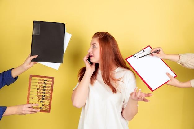 Data limite. retrato de mulher jovem caucasiana em fundo amarelo do estúdio, muitas tarefas. como gerenciar o tempo certo. conceito de trabalho de escritório, negócios, finanças, freelance, autogestão, planejamento.