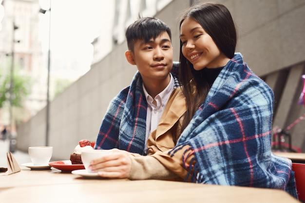Data romântica asiática de sorriso da menina e do menino no café.