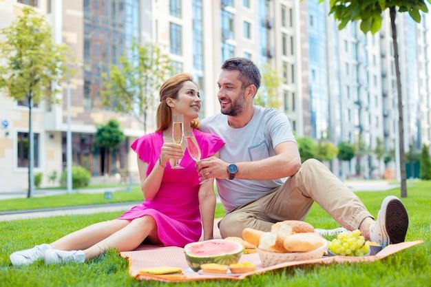 Data romantica. casal simpático e alegre bebendo champanhe enquanto faz um piquenique