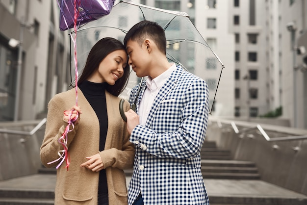 Data romântica em dia chuvoso casal asiático na rua.
