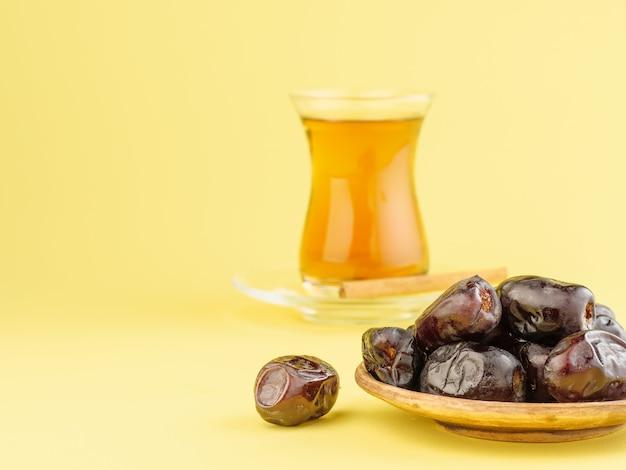 Datas com chá preto em um fundo amarelo. comida iftar tradicional durante o ramadã.