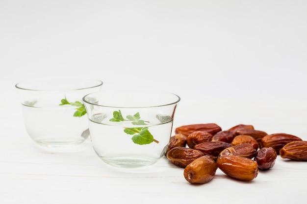 Datas de frutas com água em taças