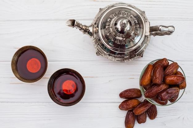 Datas de frutas com bule e xícaras na mesa