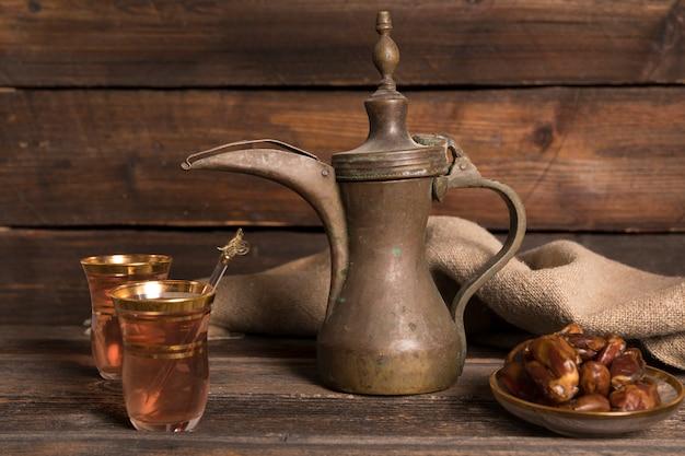 Datas de frutas com copos de chá e pote na mesa