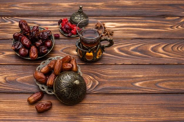 Datas de frutas no prato com copo de chá preto