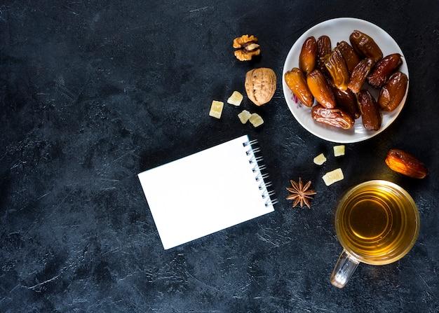 Datas de frutas no prato com o bloco de notas e chá