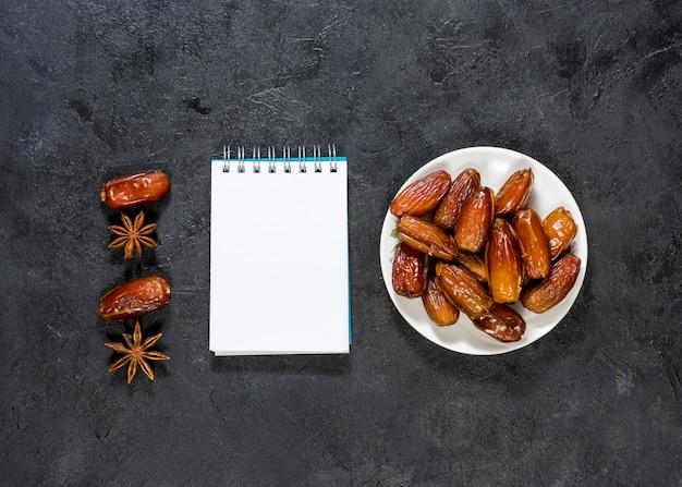 Datas de frutas no prato com o bloco de notas em branco