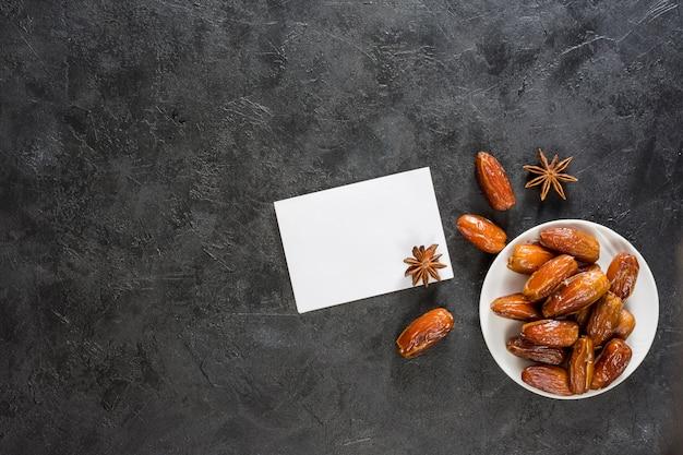 Datas de frutas no prato com papel em branco