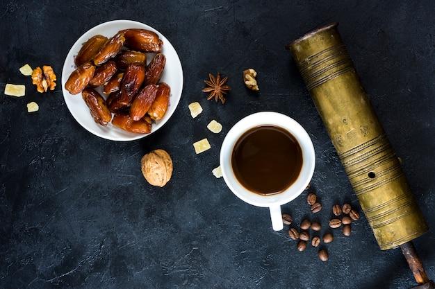 Datas de frutas no prato com uma xícara de café