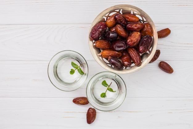 Datas de frutas no prato pequeno com água em taças