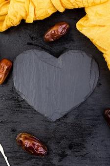 Datas de frutas secas no copo de ouro perto de coração de ardósia preta.