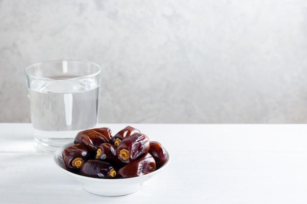 Datas e um vidro da água na tabela de madeira branca - ramadã, alimento de iftar.