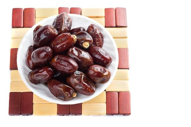 Datas em uma tigela sobre um fundo branco. frutas secas de tâmaras.
