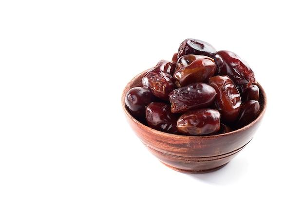 Datas em uma tigela sobre uma superfície branca. frutas secas de tâmaras.