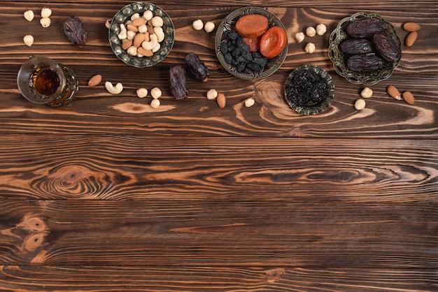 Datas frescas do ramadã; frutas secas; nozes e chá de ervas de vidro na mesa de madeira