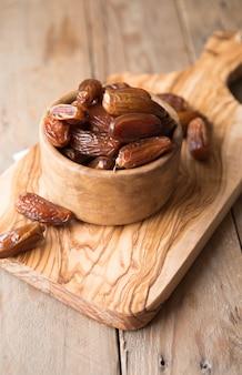 Datas frutas da palma em uma tigela de madeira é lanche saudável.